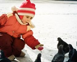 Child feeding doves in the city street winter.