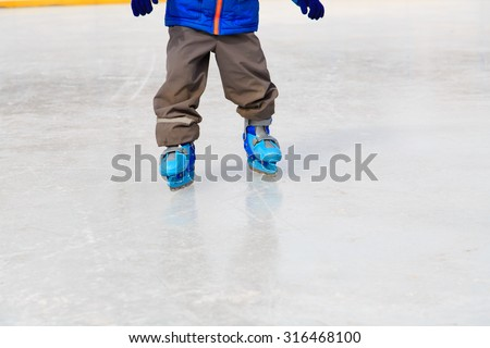 child feet learning to skate on ice in winter snow