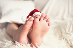 Child feet with santa hat on big toe. Big toe with face. Christmas and barefoot concept with copy space.