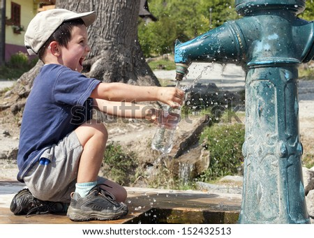 Child filling water bottle from a hydrant fountain.