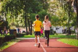 Child fitness, twins kids running on stadium track in city park , training and children sport healthy lifestyle. Outdoor activities by running make the child's body healthy and experience enriched.