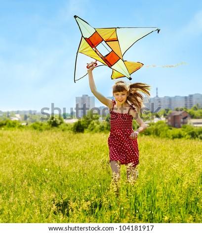 Child flying kite outdoor. little girl running across  green grass.