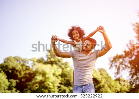 Child flying on father shoulders while held piggyback #525222922