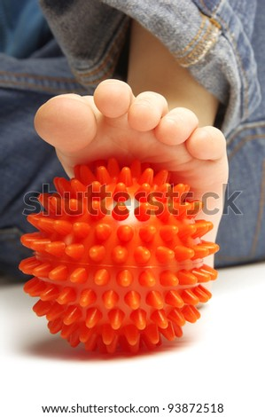 Child foot with spiny plastic orange massage ball on white background