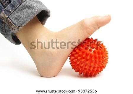 Child foot with spiny plastic orange massage ball on white background