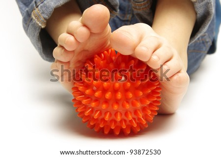 Child foots with spiny plastic orange massage ball on white background