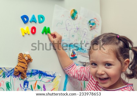 child forming mom and dad words with magnetic letters on refrigerator door. #233978653