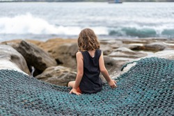 Child from behind sitting on metal netting, overlooking the ocean