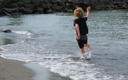 Child fully clothed running through water close to shore along the beach