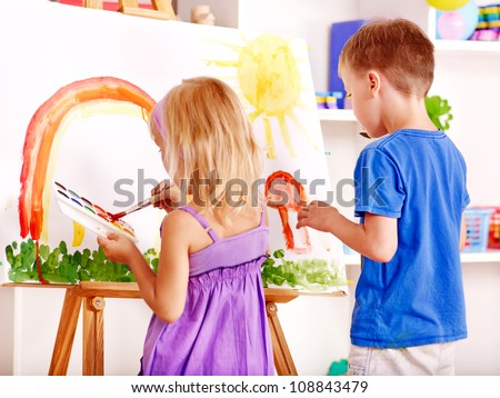 Child girl and boy painting at easel in school.