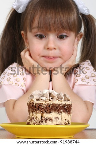 Child girl and cake, focus on cake