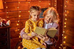child girl and grandmother reading a book in living room, spend time together, new year garlands in the background