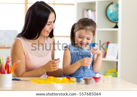 child girl and mom play with color dough at home #557685064
