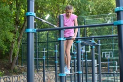 child girl doing outdoor exercise. little girl teenager gymnast is actively involved in sports outside. smortsgirl on the playground in park
