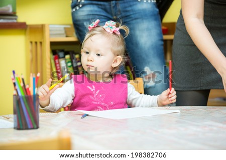 Child girl drawing with colorful pencils in preschool at the table. Little girl and boy drawing in kindergarten