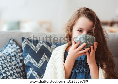 child girl drinking hot tea to recover from flu. Healing kids and protect immunity from seasonal virus, health concept #1028836789