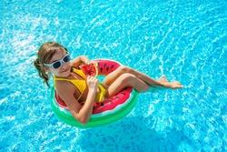 Child girl eats watermelon near the pool. Selective focus. Kid.
