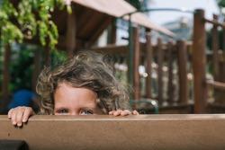 Child, Girl, hidden behind bench smiling. Daylight scene, playground.