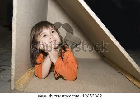 Child girl hiding in wooden box, dreams alone (series Children) - stock photo