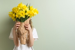Child girl holding bouquet of yellow flowers.