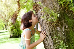 Child girl hugging kissing mature textured tree trunk in sunny forest park, smiling with eyes shut, love nature. Kid caring and protecting organic eco climate change resources. Healthy wellness planet
