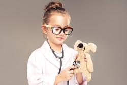 Child girl in a medical gown and stethoscope plays and pretends to be a doctor . Children choose a profession for the future. Happy and smiling baby in the game. Expressive facial emotions
