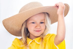 Child girl in a straw hat in yellow clothes, summer photo. on a white background