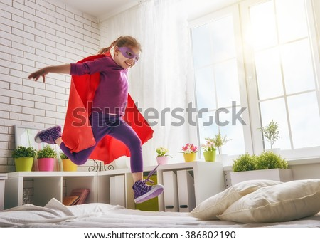 Child girl in an Superman\'s costume plays. The child having fun and jumping on the bed.