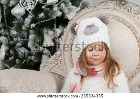 Child girl in bear hat dreaming with closed eyes and sitting on background of Christmas tree