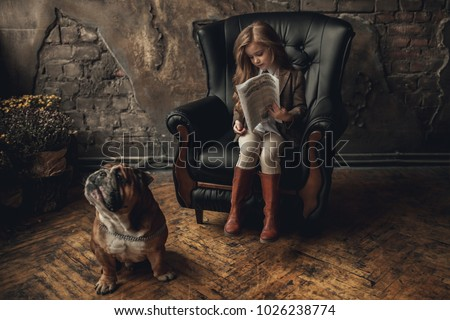 Child girl in image of detective sits in armchair and reads newspaper next to English bulldog on background of old brick walls and shabby parquet floor.