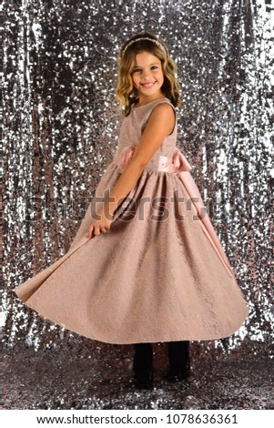 Child girl in stylish glamour dress, elegance. Fashion model on silver background, beauty. Fashion and beauty, little princess. Look, hairdresser, makeup. Little girl in fashionable dress, prom. #1078636361