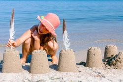 Child girl in summer hat is decorating sand towers, figure with seagull feathers.