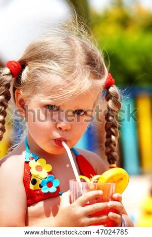 Child girl in sunglasses and red bikini drink orange juice.