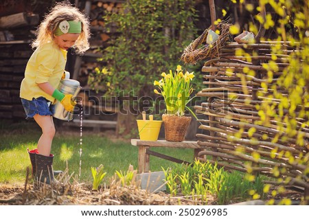 child girl in yellow cardigan watering flowers in spring garden