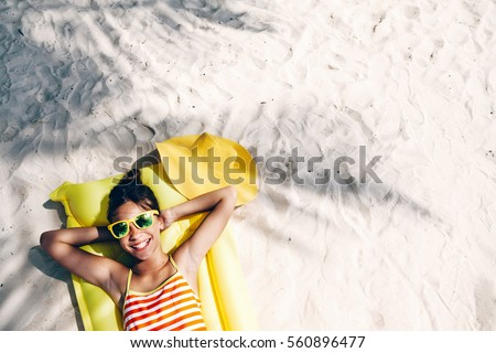 Child girl in yellow swimwear and sunglasses chilling on lilo under palm tree on sand at the beach. Tropical island. Summer holiday idyllic. Top view.