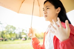 Child girl is holding umbrella uv protection from sunlight ray,high temperature on sunny day,prevent heatstroke,face skin from bright sun,sunburn very hot,using umbrella to cover the strong sun light