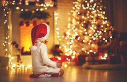 child girl is sitting with her back in front of Christmas tree on Christmas Eve