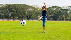 Child girl kick the ball away while training football on the field
