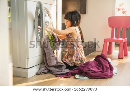 child girl little helper in laundry room near washing machine and dirty clothes. Cute little girl doing laundry at home. child fun happy little girl to wash clothes and laughs in the laundry room.