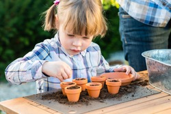 child girl planting flower seeds with mother. Gardening, planting concept - mother and daughter planting flower seeds  into small pots
