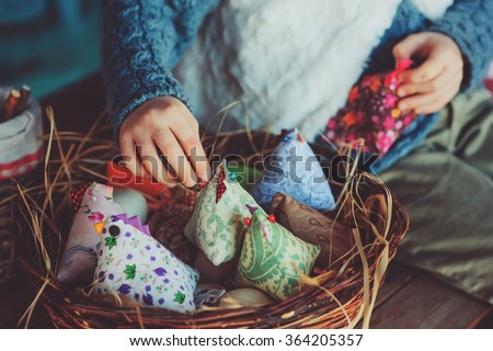 child girl playing with easter eggs and handmade decorations in cozy country house - stock photo