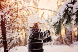 child girl playing with snow on winter forest walk. Cozy mood, seasonal outdoor activities.