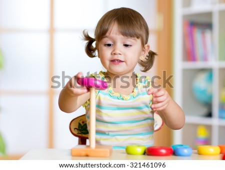 Child girl playing with toy indoors at home stock photo
