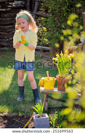 child girl plays little gardener and wearing rubber gloves in spring