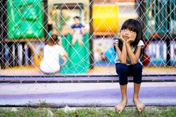 Child girl sitting lonely watching friends play at the playground
