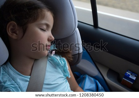 Child girl sleeping in a child safety seat during trip. She's got a brick milkshake on car door #1208380450