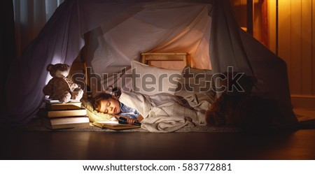 child girl sleeping in a tent with a book and a flashlight home