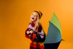 child girl smiling in a bright multicolored sweater and hat holding an umbrella stands on a yellow background. little girl in bright clothes is holding a red-colored umbrella. happy child, space for