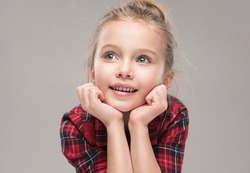Child girl surprised holds her face and dreamily looks to the side. Little Baby  in a red dress. Children's products , clothing and accessories . Expressive facial emotions