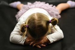 Child girl upset lying on the floor and crying on a black background